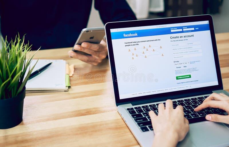 曼谷,泰国- 2017年8月23日:妇女演奏显示屏幕facebook的膝上型计算机 facebook最大和最普遍的社交n 库存图片