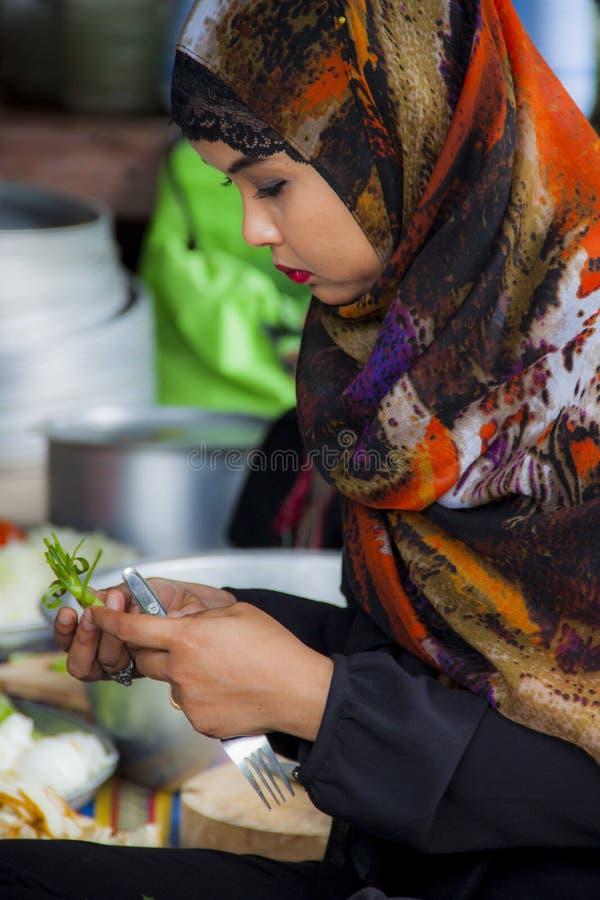 曼谷,泰国8月2014年-泰国回教女孩成份食物为烹调Mussaman辣椒咖喱沙拉做准备 库存图片