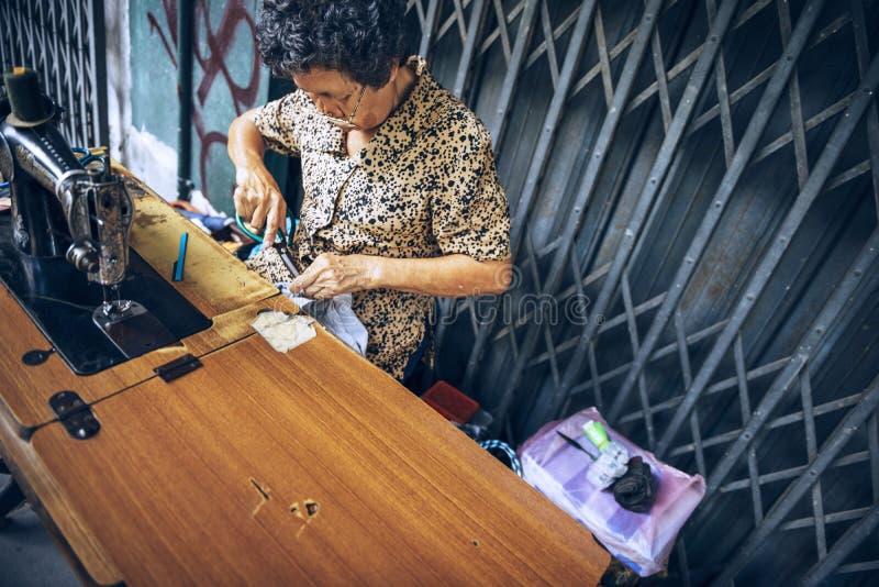 曼谷,泰国- 6月04 :亚裔老妇人裁缝是sewin 免版税库存图片