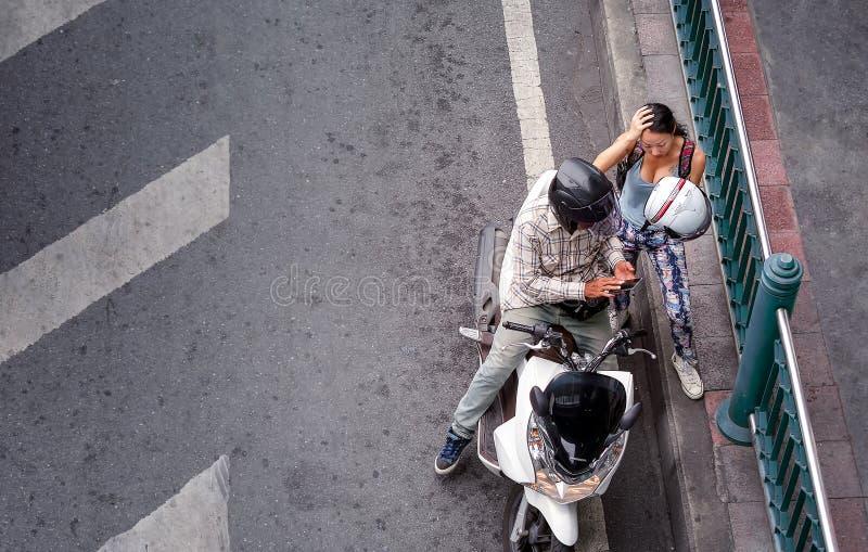 曼谷,泰国- 6月29:无提名的夫妇临时地拉扯了对路的边有本田PCX滑行车摩托车的  免版税库存图片