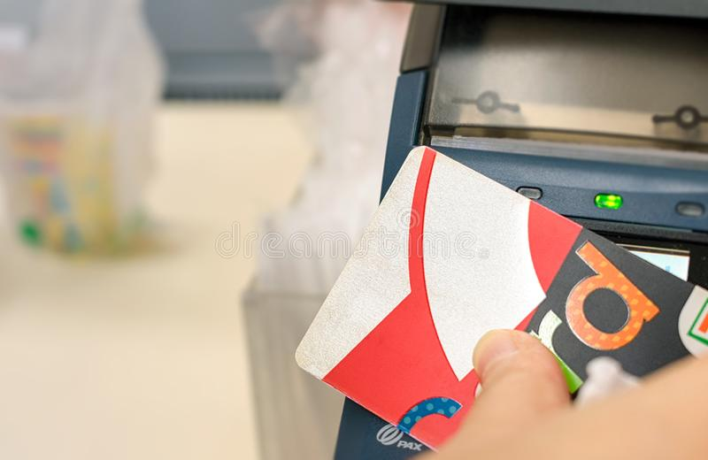 曼谷,泰国- 12月23:顾客在曼谷使用7-Eleven现金卡付付款在地方7-Eleven便利店 免版税图库摄影