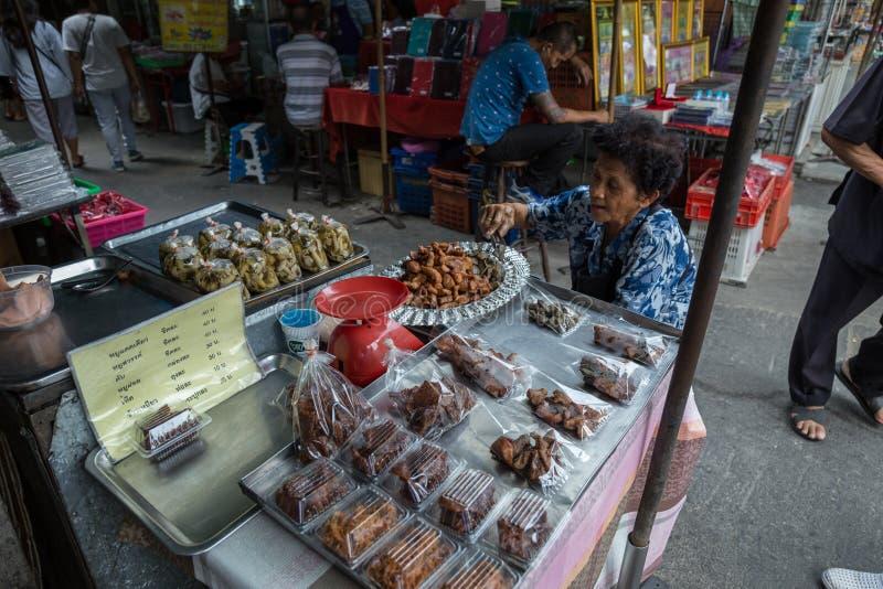 曼谷/泰国- 2018年3月24日:老人卖食物作为油煎的猪肉,在码头Tha Prachan路 库存照片