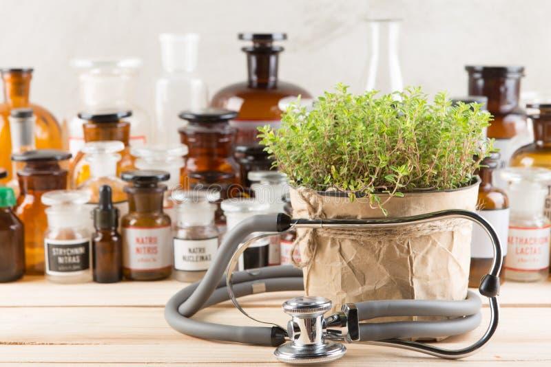 替代医学在瓶、医药草本和听诊器的概念医学在一张木桌上 库存图片