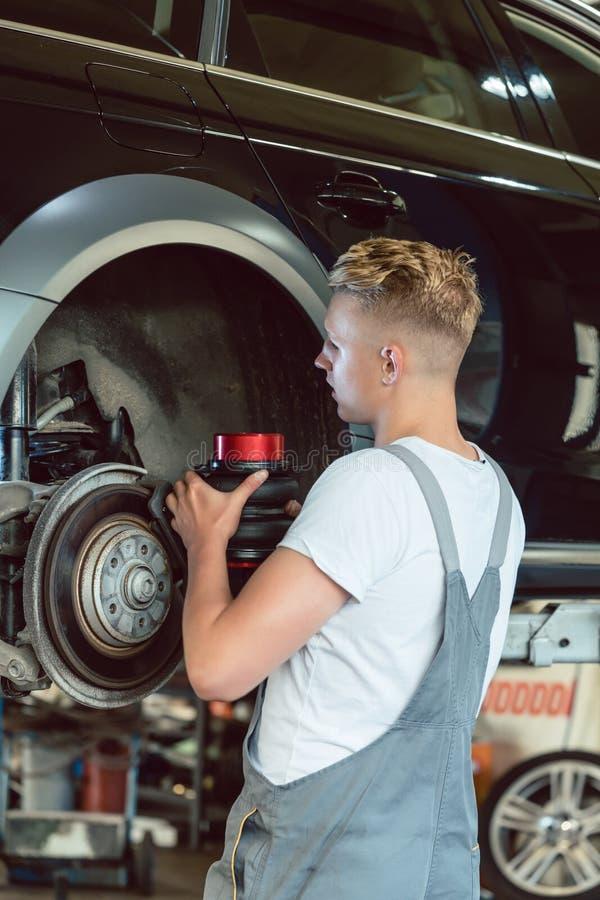 替换一辆汽车的圆盘制动器的在一个现代维修车间的老练的技工 免版税库存图片