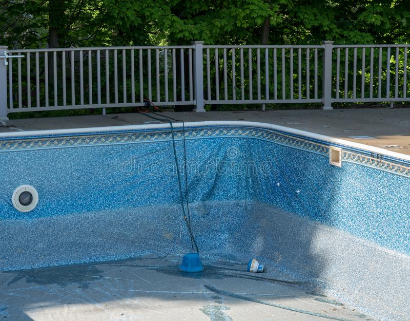 替换和修理游泳场老乙烯基衬垫  免版税库存照片