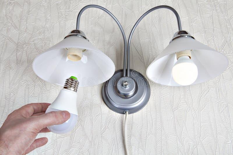 替换在墙壁光的电灯泡,手拿着LED灯 库存图片