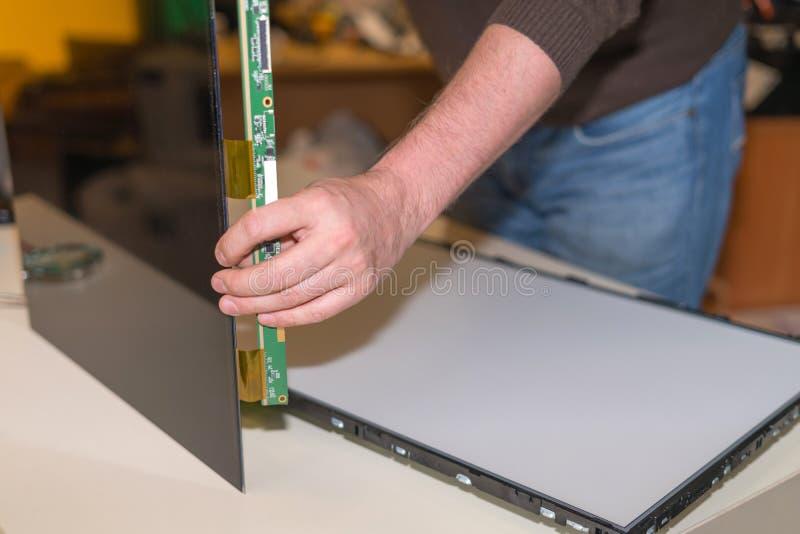 替换在现代LCD电视的屏幕用LED由后照在服务中心 库存图片