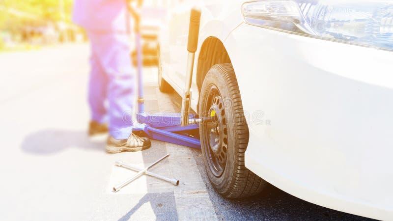 替换在路的汽车修理师泄了气的轮胎 蓝色水力汽车地板用千斤顶压出或拔出器拔出汽车,并且轮子板钳附近安置了 库存图片