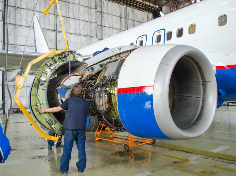 替换在飞机上的引擎,工作者轻拍 航空器概念维护  库存图片