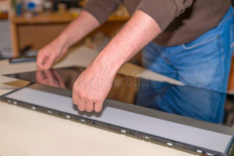 替换在LCD电视的屏幕,修理电视,实际工作服务中心 免版税库存图片
