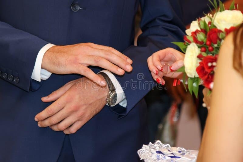 替换敲响婚礼 新娘在新郎` s手安置圆环 库存图片