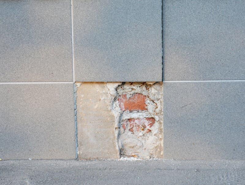 替换残破的瓷瓦片地板的部分 用新的瓷瓦片替换老巴恩砖地 库存照片