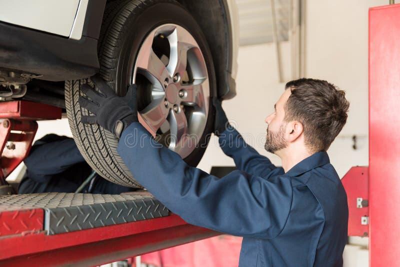 替换车胎的技工在汽车修理店 免版税库存照片