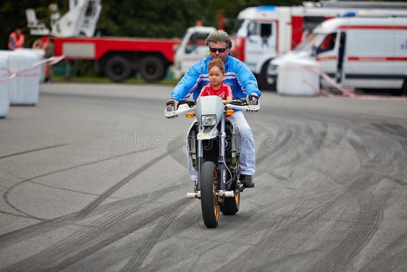从替身演员的成员合作有孩子的乘驾摩托车 免版税库存图片