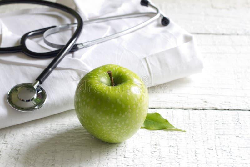 替代医学听诊器和绿色标志背景 免版税库存图片