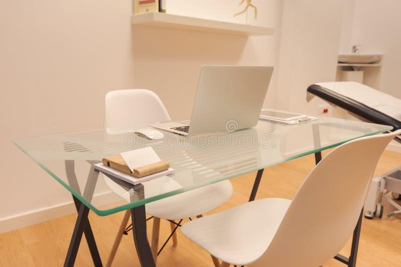 最低纲领派办公室内部有白色墙壁的、木地板、木和玻璃计算机桌和白色书橱有文件夹的 库存图片