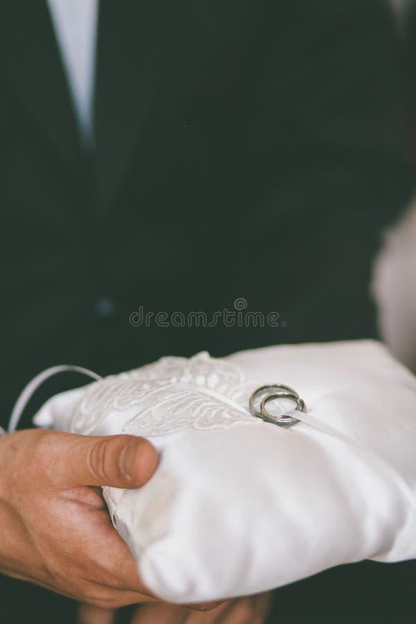 最佳的人拿着有结婚戒指的一个枕头 免版税库存图片