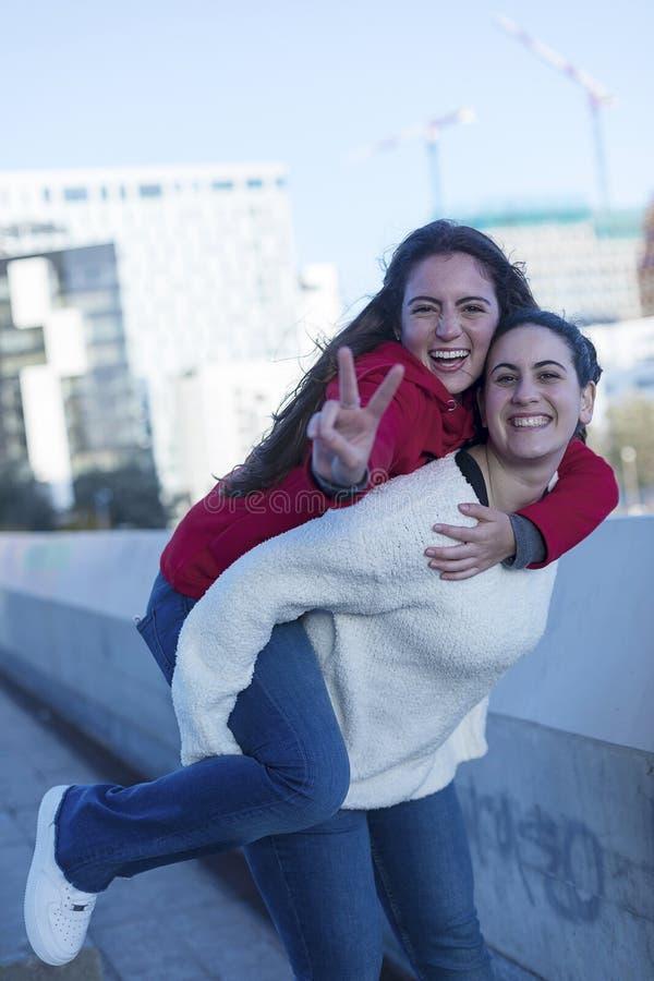 最佳的微笑的朋友女孩正面图在城市扛在肩上户外 免版税库存照片