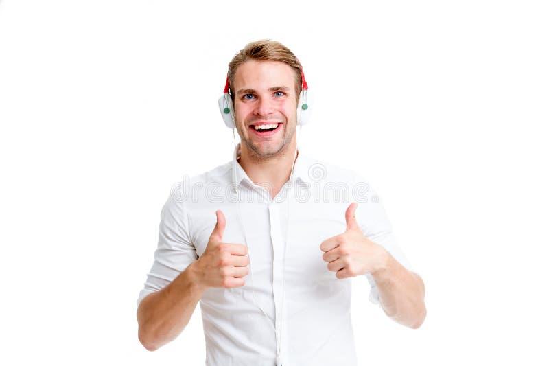 最佳的歌曲  在耳机的人听的喜爱的歌曲显示赞许 人愉快的面孔享用听的音乐收音机 图库摄影