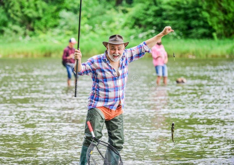 最佳的片刻 成熟人钓鱼 夏天周末 有钓鱼竿的渔夫 猎人 人捉住的鱼 ?? 免版税图库摄影