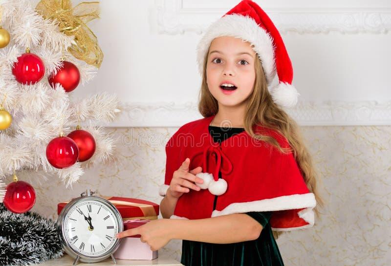 最后一刻的实际上是全部乐趣的除夕计划 女孩孩子圣诞老人有计数时间的时钟的帽子服装对新 免版税图库摄影