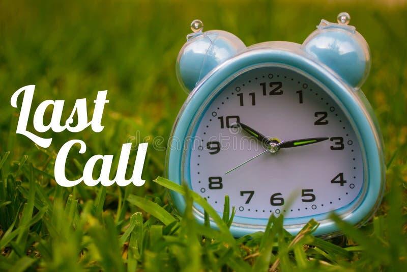 最后呼叫,企业概念-发短信给显示与一个时钟的最后呼叫在草 库存照片