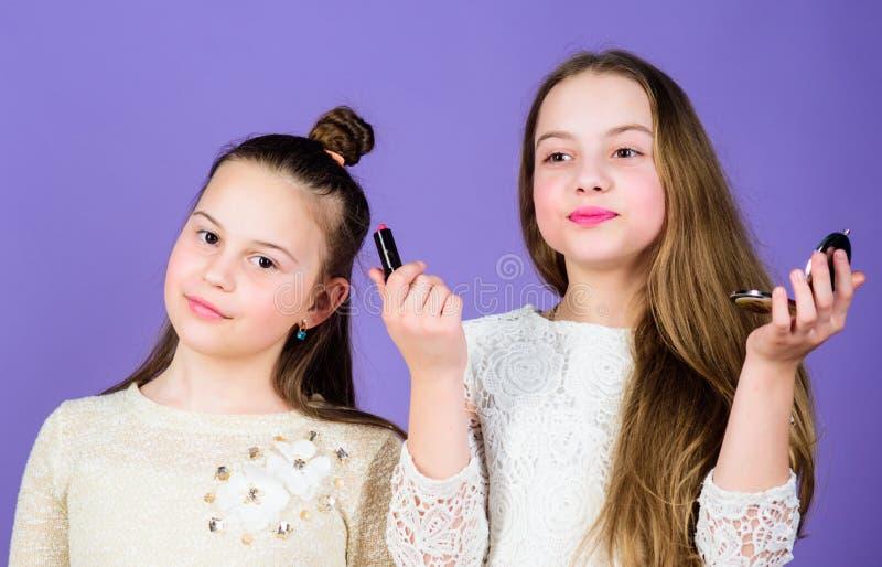 最好做和美容品 组成拿着唇膏和紧凑粉末的艺术家 佩带面孔的逗人喜爱的小女孩 免版税库存图片