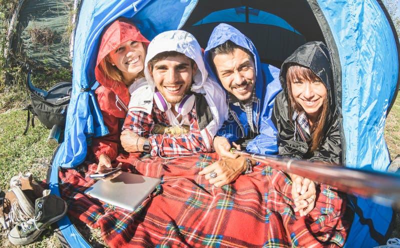 最好的朋友在晴天结合采取selfie在野营的帐篷 免版税库存照片