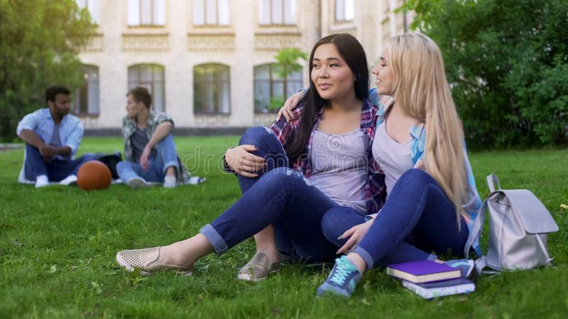 最好的朋友坐草坪在学院,拥抱,支持和友谊附近 免版税库存照片