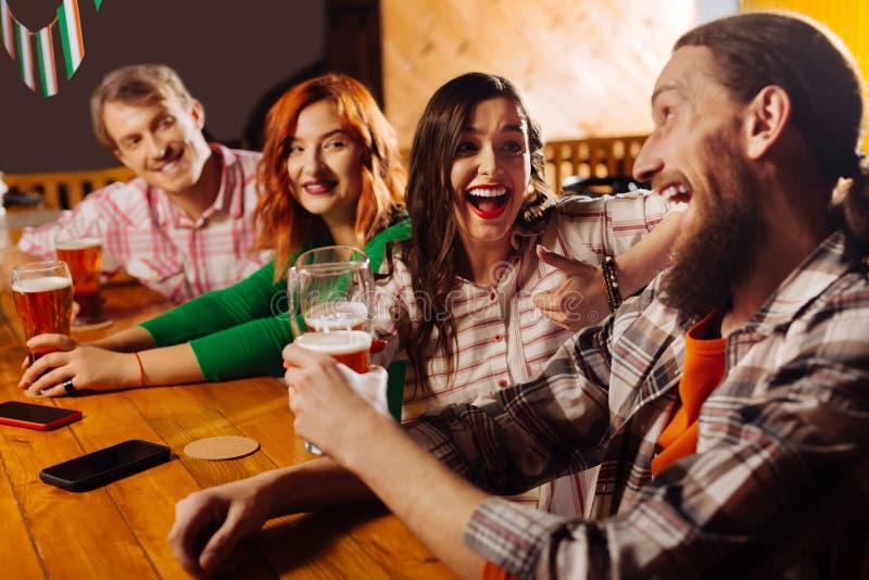 最好的朋友花费他们星期五晚上在客栈饮用的啤酒 免版税图库摄影