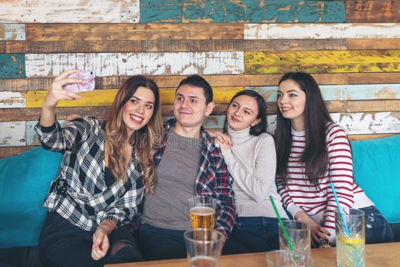 最好的朋友采取selfie和获得乐趣在土气酒吧-青年和友谊概念 库存图片