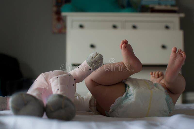 最好的朋友:愉快的婴孩和玩具` s脚 免版税库存照片