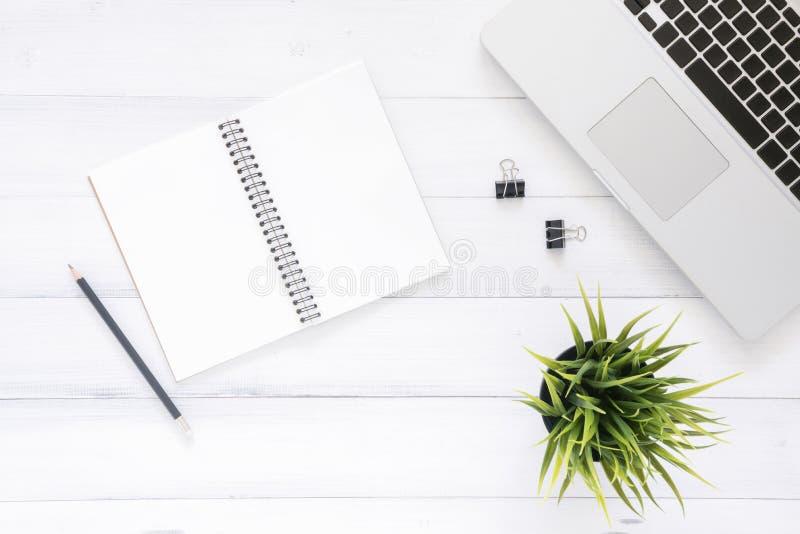 最小的工作区-创造性的舱内甲板放置工作区书桌照片  顶视图有膝上型计算机的办公桌,嘲笑笔记本和植物 免版税库存照片
