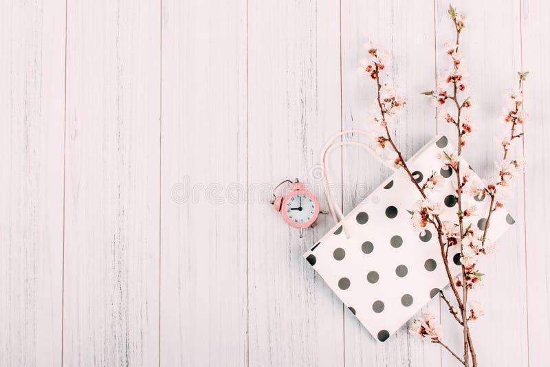 最小的现代购物的销售背景,横幅 与花、购物带来和桃红色闹钟的开花的樱桃分支在光 库存图片
