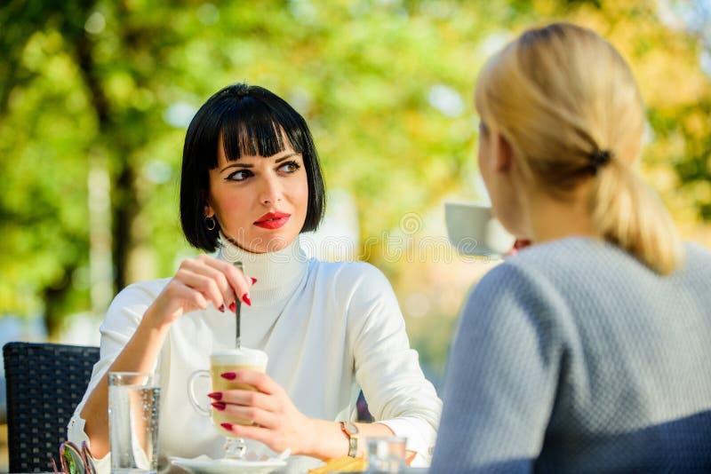 最接近的人民 女朋友喝咖啡谈话 交谈妇女咖啡馆大阳台 友谊友好的联系 库存图片