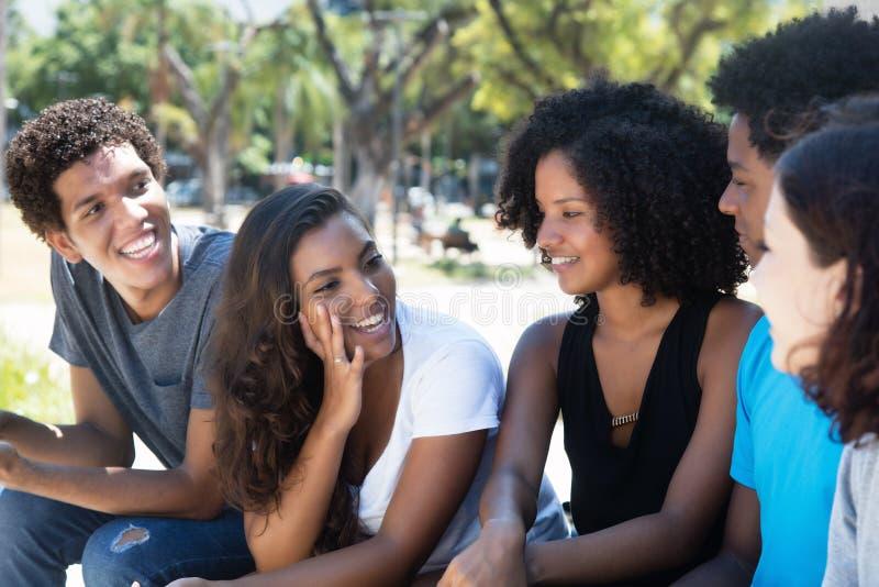 最新妇女和非洲人谈话与白种人朋友 库存图片