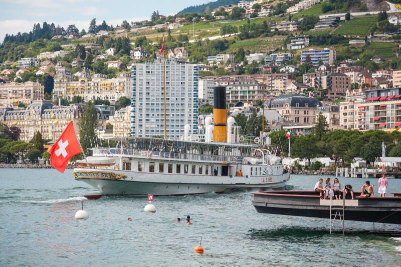 最美的蒸汽船叫瑞士拉船,瑞士国旗在靠近瑞士里维埃拉的蒙特勒码头的船尾挥舞, 库存图片