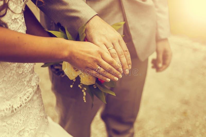 最近婚姻夫妇有婚戒的` s手 葡萄酒口气 图库摄影
