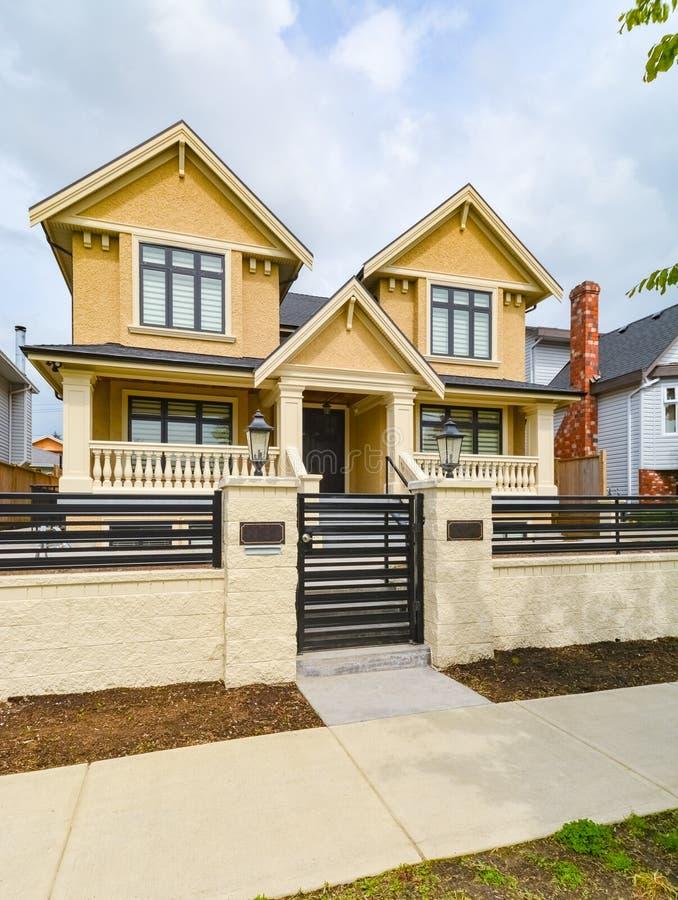 最近被更新的豪华住宅房子待售 有具体路和金属篱芭的大家庭房子 免版税库存图片