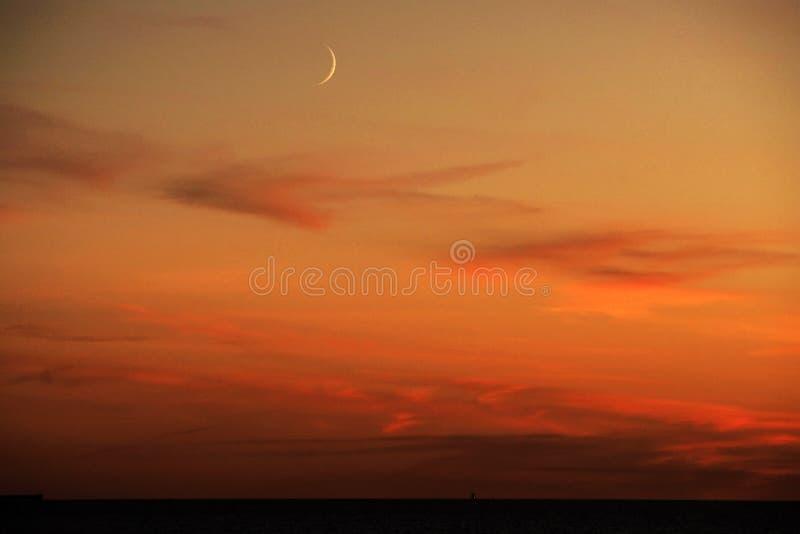 月亮和红色云彩在日落以后 免版税图库摄影