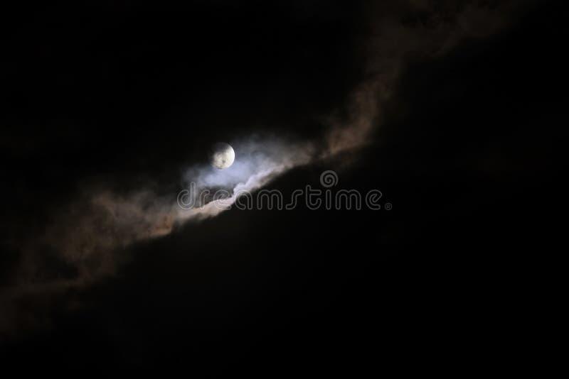 月亮在云彩后发光在黑暗的夜空,背景 库存照片