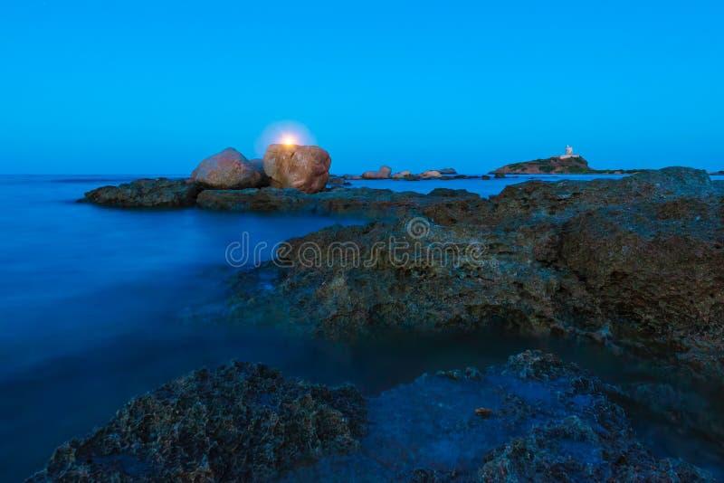 月亮广角看法在海景、岩石和灯塔的 库存图片