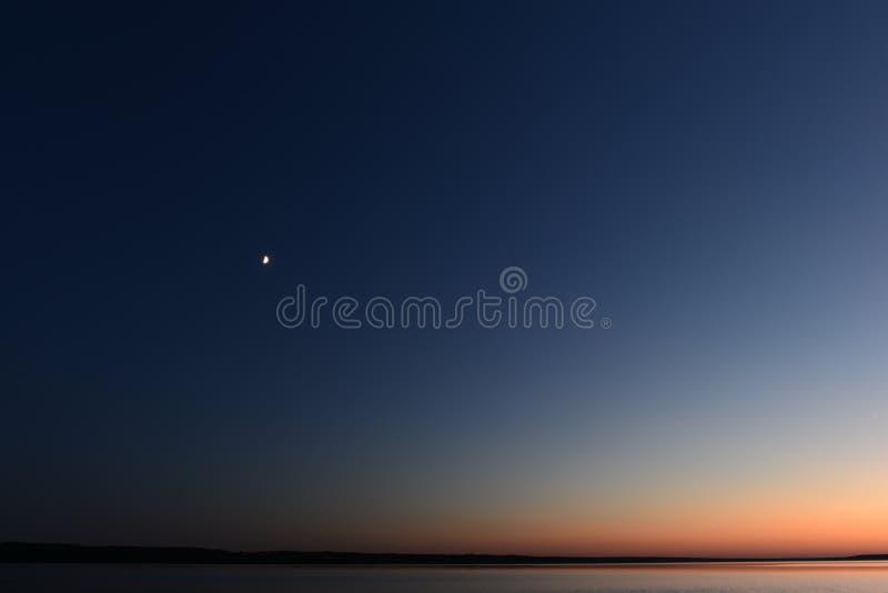月亮的月光在蓝色黑暗的夜空的在湖上 免版税库存图片