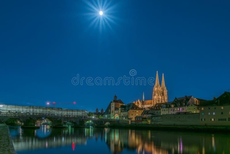 满月夜在雷根斯堡巴伐利亚有覆以圆顶圣皮特圣徒・彼得、石桥梁和河的看法多瑙河 库存照片