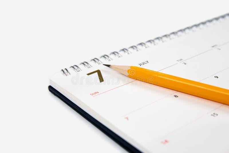 7月日历和铅笔在白色背景 库存照片