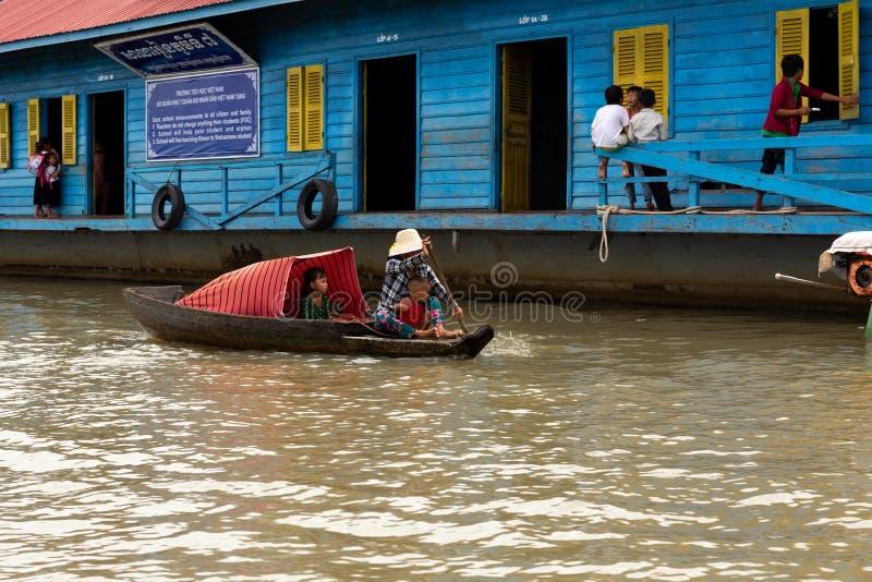 8月:29 :把孩子带的2018年-暹粒,柬埔寨-母亲对学校乘小船在Tonle Sap湖的浮动村庄 免版税库存图片