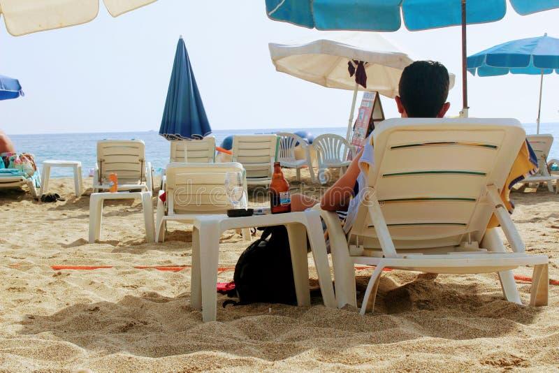 2017年7月-一个人休息与啤酒说谎在的一个瓶sunbed在帕特拉海滩阿拉尼亚,土耳其 库存图片