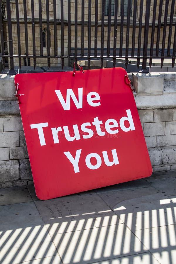 7月2019我们信任您亲的Brexit标志紧固了到篱芭在有在边路写的某一亵渎的伦敦在阴影 免版税图库摄影