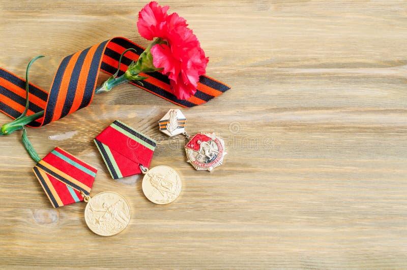 5月9日与巨大爱国战争、红色康乃馨和乔治丝带奖牌的欢乐背景  免版税库存照片
