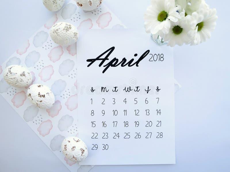 4月2018日历、复活节彩蛋和白花 图库摄影